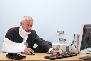 Photo of a mature businessman with multiple injuries sitting at his desk struggling to work on his computer. Good image for health and safety, accident at work or healthcare insurance related themes. Puyallup Personal Injury Lawyer